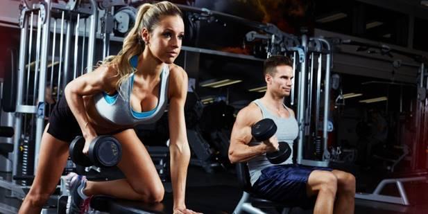 Jenta og fyren i treningsstudioet utfører øvelser
