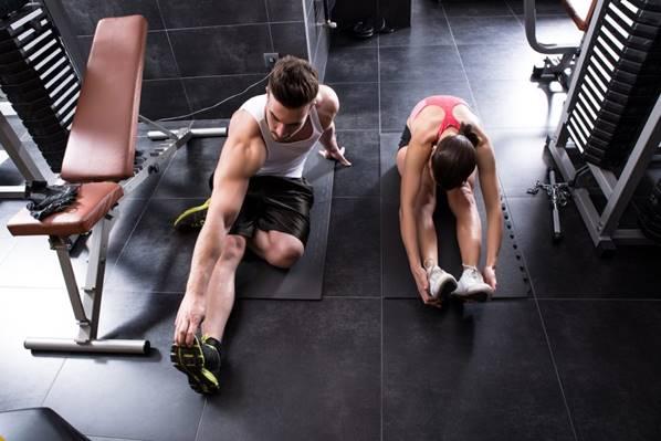 Mann og kvinne strekker seg i treningsstudioet